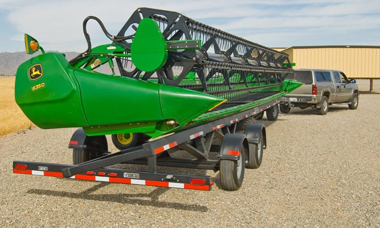 A custom trailer carries a John Deere harvesting attachment behind a pick-up truck