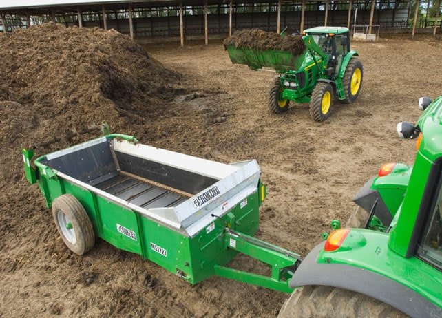 John Deere tractor about to load a Frontier MS12 Series Manure Spreader