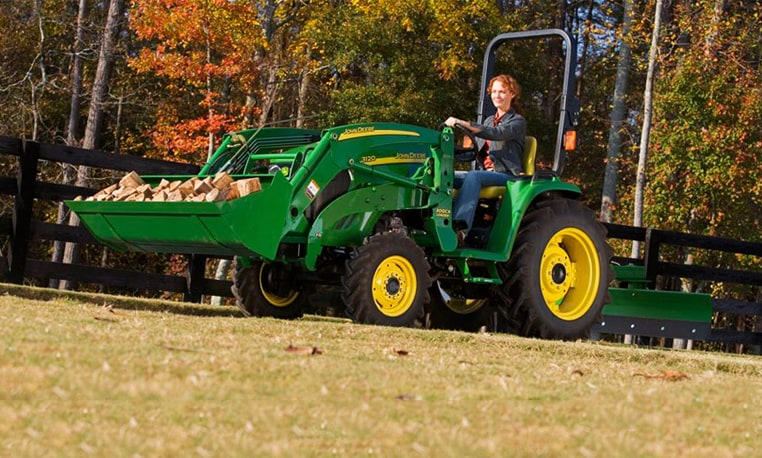 Woman using a John Deere utlity tractor with loader attachment