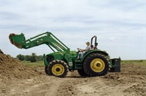 Man using a 542 Self-Leveling Loader to lift a bucket of dirt
