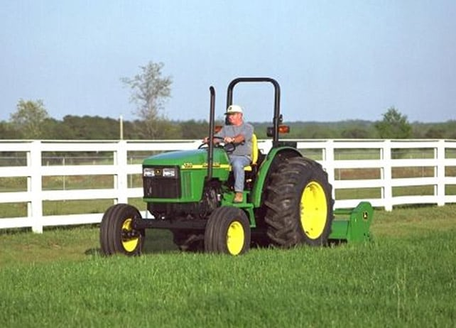 Man using a John Deere tractor with Flail Mower attachment to cut grass next to a white fence