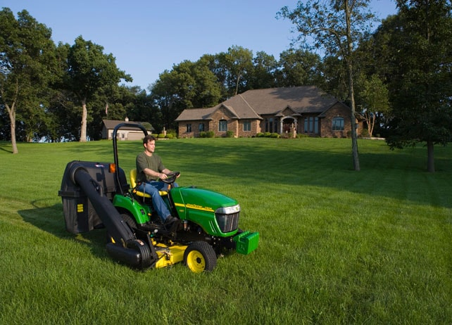 Man using a 54C Mid-Mount Side Discharge Mower to cut a large lawn with a house in the background