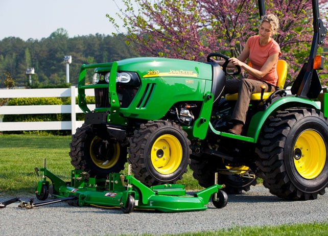 Woman attaching the 54D OnRamp™ Mid-Mount Mower to her tractor