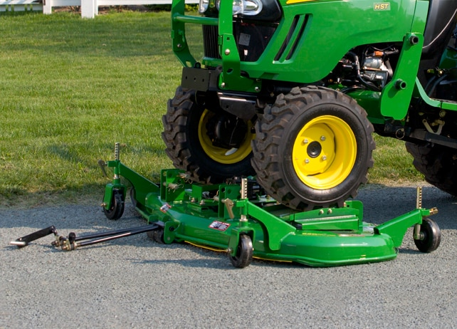Closeup of a John Deere tractor attaching a 62D OnRamp™ Mid-Mount Mower