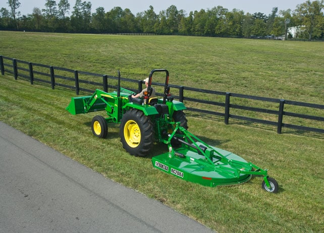 Overhead rear view of a man using the Frontier RC20 Series Rotary Cutter to cut grass next to a road