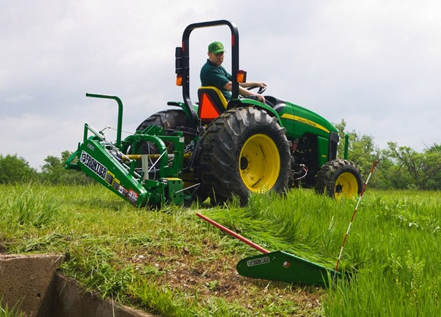 Man using a Frontier SB31 Sickle Bar Mower to cut long grass near a culvert