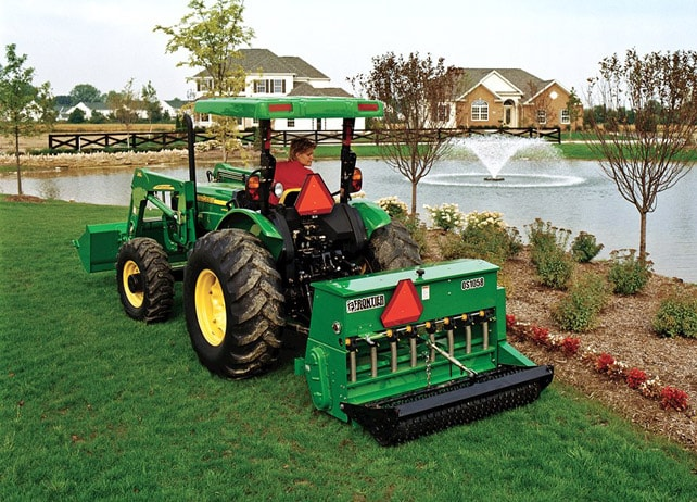 Woman operates a Frontier TR20 Series Overseeder around a residential lake