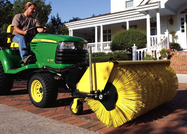Man uses a 52-inch Quick-Hitch Rotary Broom to clean debris from a brick sidewalk