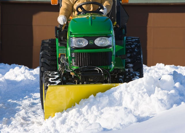 Front view of a 54-inch Front Blade plowing snow