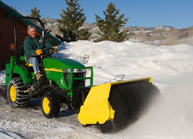 Man uses a 60-inch Heavy Duty Rotary Broom to clear snow from a driveway