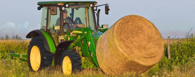 John Deere tractor hauling a hay bale through a field