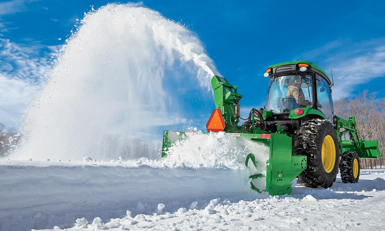 Tractor using snow blower to remove snow