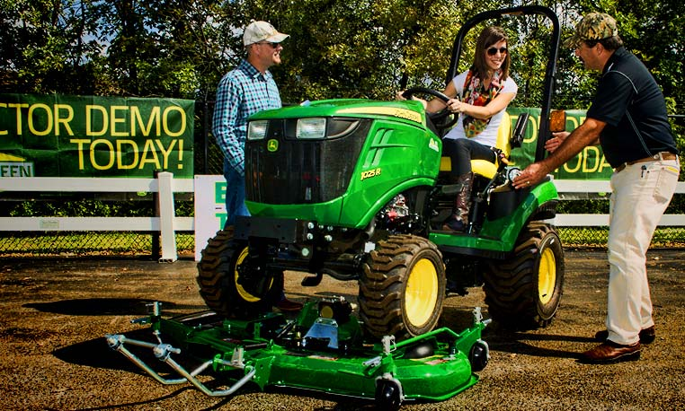 Woman on John Deere Tractor test driving mow-over deck