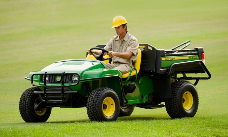 Individual operating a gator on a golf course