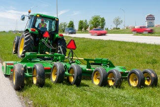 John Deere Tractor with cutting attachment mowing grass in the median of a highway