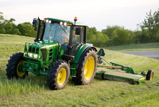 John Deere Tractor with Rotary Cutting attachment working in a grassy field