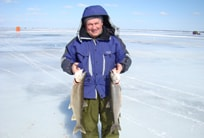 Smiling ice fisherman holding up two large fish