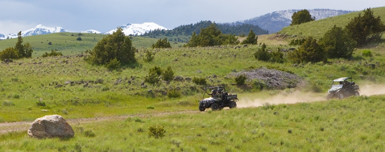 Two Gator Utility Vehicles drive through mountainous terrain