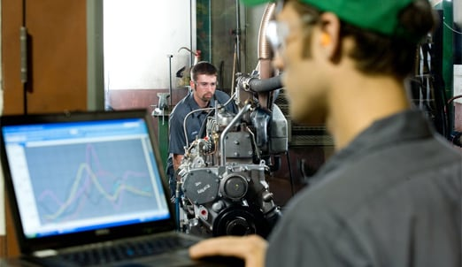 One man operates a computer in the foreground while another man checks an engine in the background