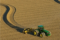 John Deere tractor leaves a winding trail of groomed soil behind