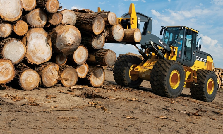 A John Deere wheel loader uses a log fork attachment to move logs