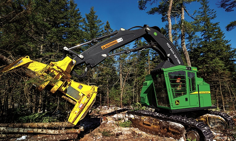 John Deere feller buncher cutting down a tree at a job site