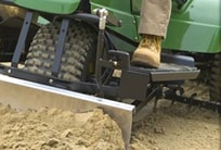Closeup of a bunker rake pushing sand in a bunker