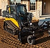 323E Compact Track Loader with a Worksite Pro Power Rake attachment