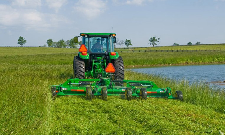 Rear view of John Deere tractor with cutter attachment trimming grass near a pond