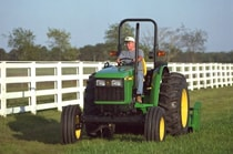 Man using a John Deere tractor with attached 25A Flail Mower to cut grass