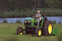 Man using a John Deere tractor with attached 370 Flail Mower to cut grass with a pond in the background