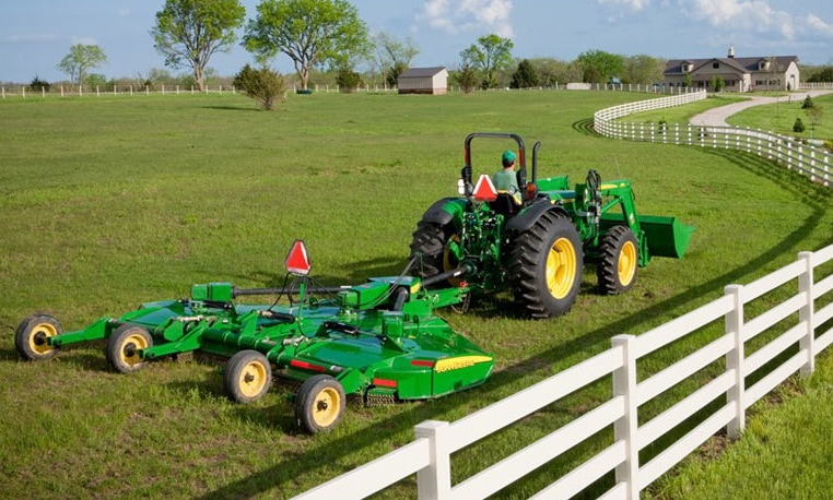 John Deere tractor using a Medium-Duty Rotary Cutter to cut grass next to a white fence