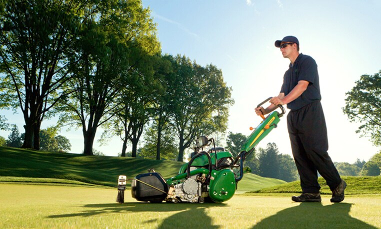 Grounds crew member uses a walk greens mower to mow a green