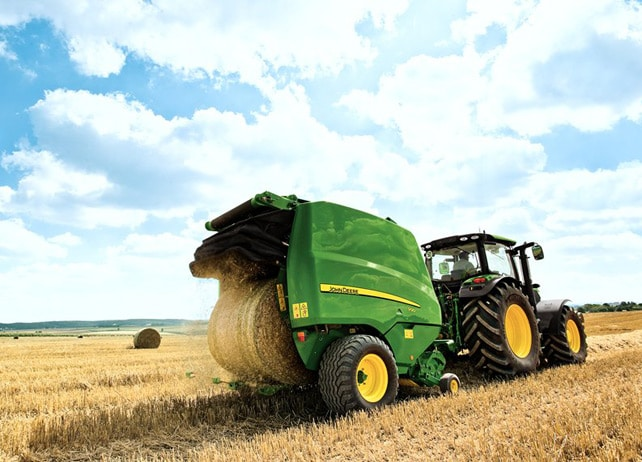 John Deere tractor with 864 Baler in field