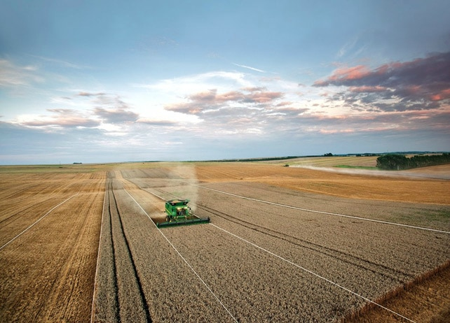 AMS: John Deere tractor in field using AutoTrac