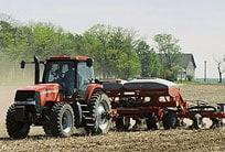 Tractor with tillage attachment plowing a field