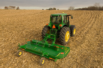 Rear view of a John Deere tractor with HX14 Rotary Cutter working in a field