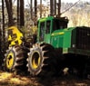 Rear view of the 643K Wheeled Feller Buncher sawing into a tree in the forest