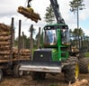 1010E Forwarder placing a group of logs on a trailer at a job site