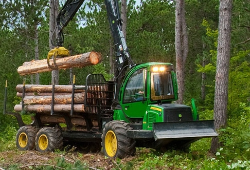 1010E Forwarder in the forest placing logs in its load center