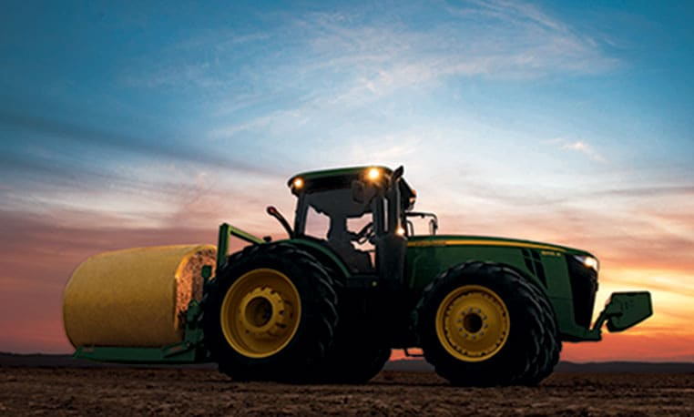 Ground-level view of a John Deere tractor at dusk