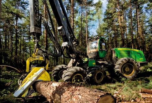 Ground-level view of the 1470E Wheeled Harvester cutting into a log at a job site