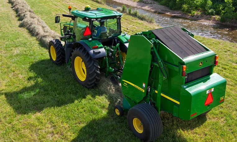 John Deere tractor and baler working in a field