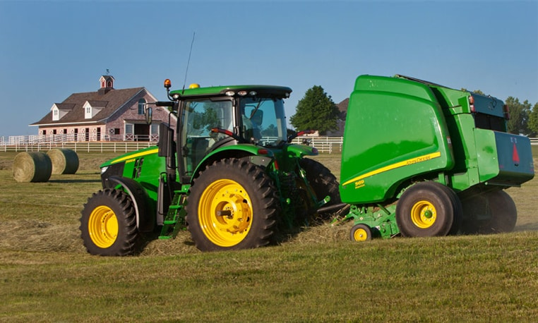 John Deere tractor with baler working in a field