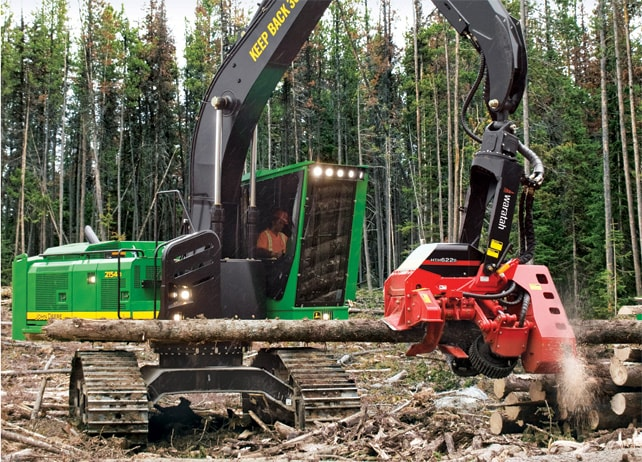 2154D Forestry Swing Machine with Waratah attachment cutting logs in a forest
