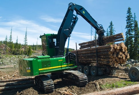 2454D Forestry Swing Machine placing logs on a trailer