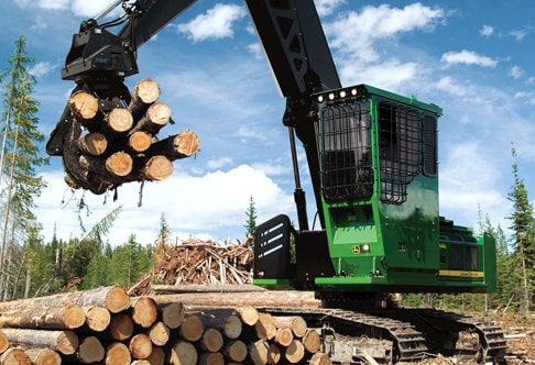 2454D Forestry Swing Machine moving a bunch of logs at a job site