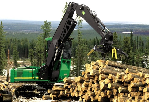 2954D Forestry Swing Machine piling up logs on a hill with trees below