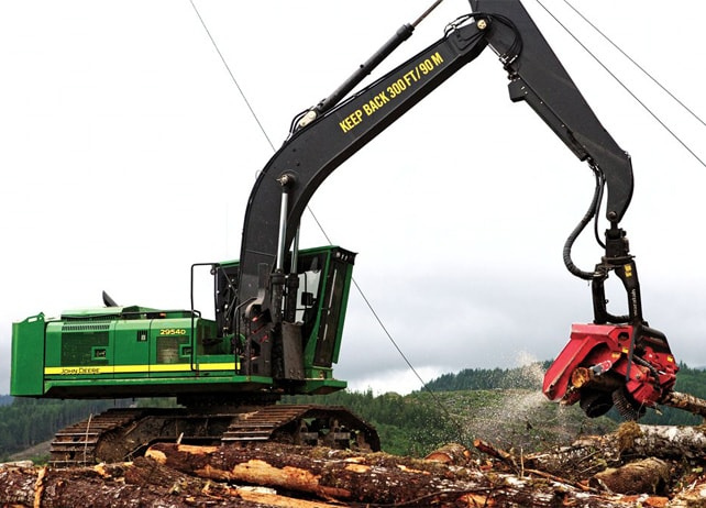 2954D Forestry Swing Machine cutting logs at a job site with mountains in the background
