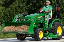 Woman driving a 2025R Compact Utility Tractor